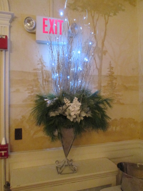 Lighted branches with greenery and white floral accessories.
